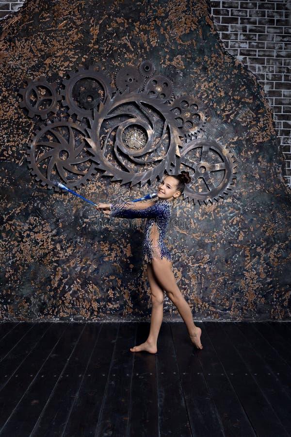 Гимнаст девушки в голубом костюме со сверкнает делающ тренировку с гимнастическими клубами стоковое изображение