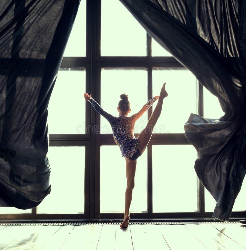 Гимнаст девушки раскрыл бодрствование вверх и занавесы и делать тренировку перед окном в утре стоковая фотография rf