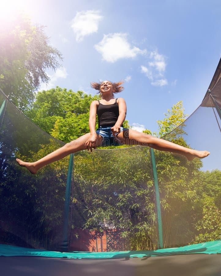 Гимнаст девушки скача на батут, делая разделяет стоковое изображение rf