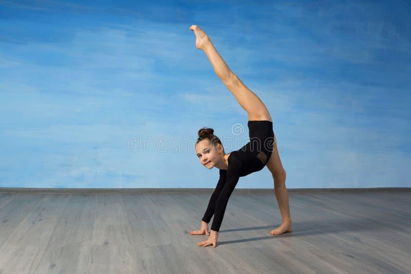 Гимнаст девушки усмехается и показывается гимнастическую тренировку на поле на голубой предпосылке Руки на поле, нога подняты вве стоковые изображения