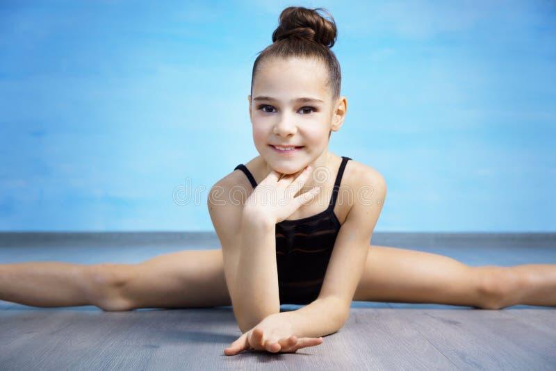 Гимнаст девушки portpait в черном гимнастическом купальнике сидит на перекрестные разделения стоковое фото