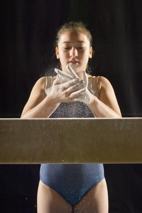 Гимнаст прикладывая белый мелок к рукам стоковые изображения rf