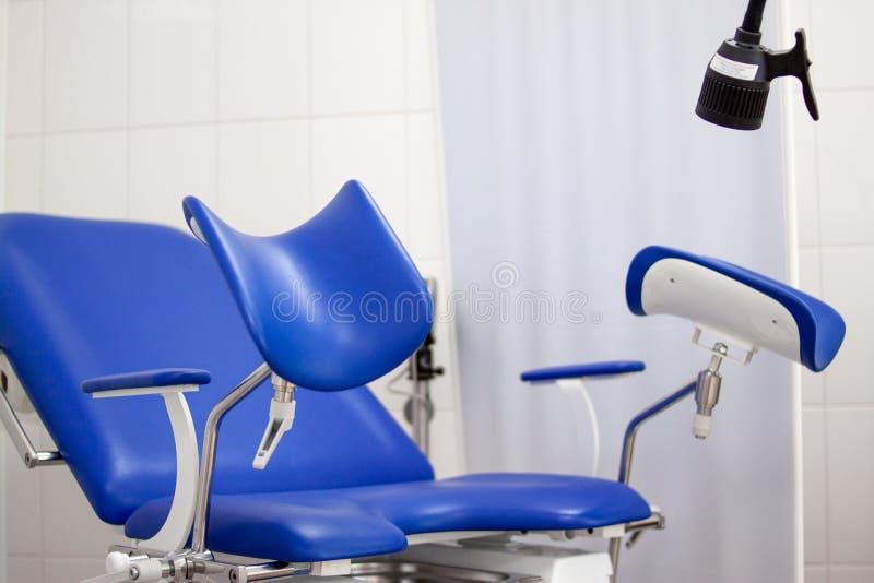 Гинекологический шкаф в больнице клиники с голубым стулом и другим медицинским оборудованием Здоровье женщины, newborn и стоковые фото
