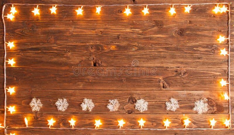 Гирлянда золота рождества теплая освещает с снежинками на деревянной деревенской предпосылке Концепция рождества или Нового Года стоковые фотографии rf