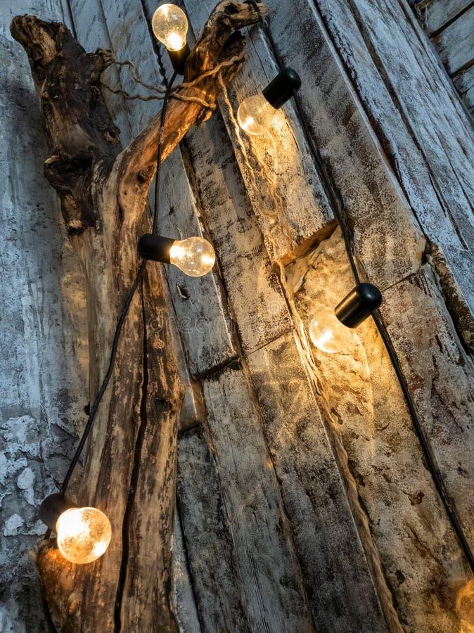 Гирлянда ламп на хоботе дерева в комнате, стене цвета свет подкрашиванных доск Желтые теплые электрические лампочки стоковые изображения rf