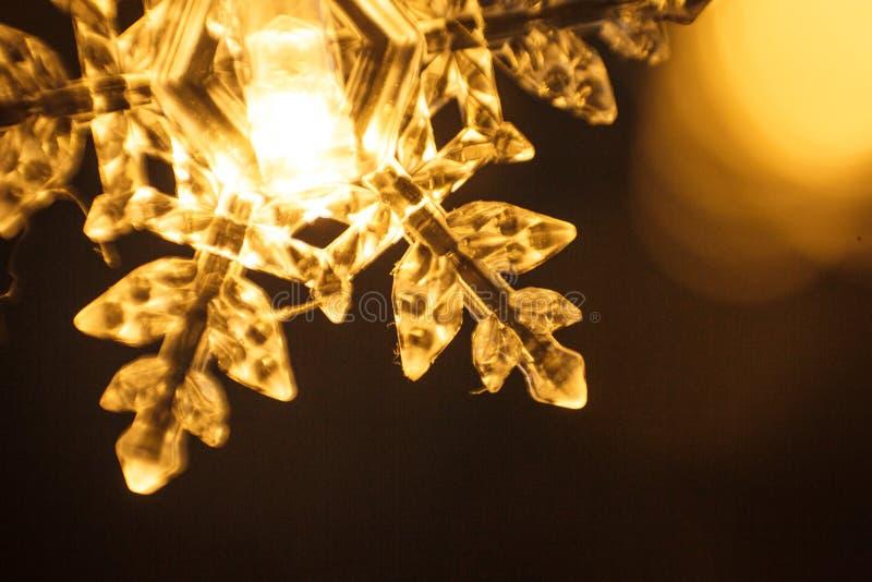 Гирлянда праздника, ясная пластиковая снежинка накаляет с золотым светом стоковое фото rf