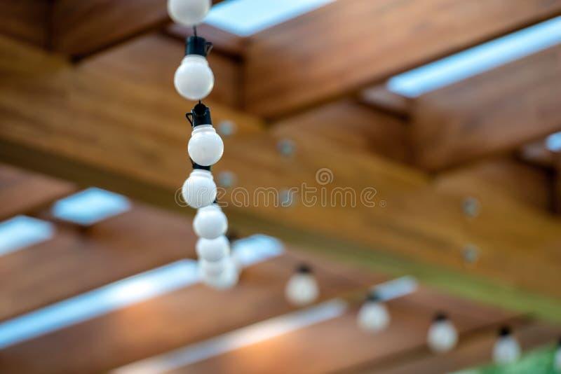 Гирлянда электрических лампочек вися под потолком в деревянном доме стоковое изображение
