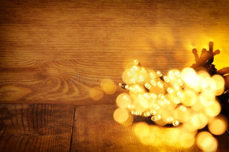 гирлянда яркого блеска освещает предпосылку черное золото де-сфокусированный стоковое фото