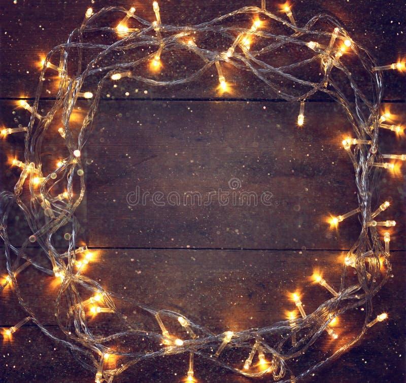 Гирлянда золота красочного рождества теплая освещает на деревянной деревенской предпосылке Фильтрованное изображение стоковые фотографии rf