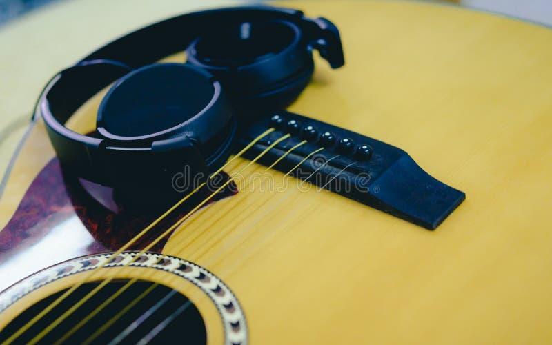 Гитара и наушники крупного плана акустическая стоковая фотография