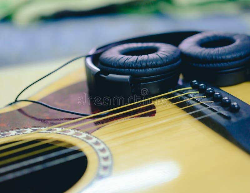 Гитара и наушники крупного плана акустическая стоковая фотография rf