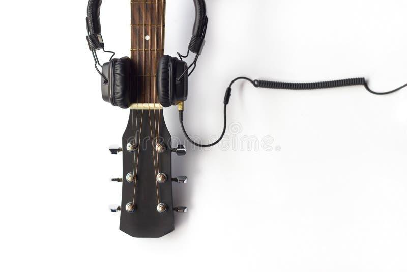 Гитара и наушники на белой предпосылке стоковые изображения