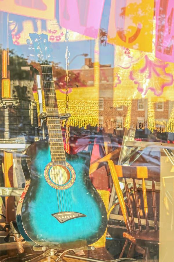 Гитара украшенная бирюзой подпирала вверх в окне магазина с отражениями и пинком и желтых смертных казнях через повешение boho по стоковое изображение rf