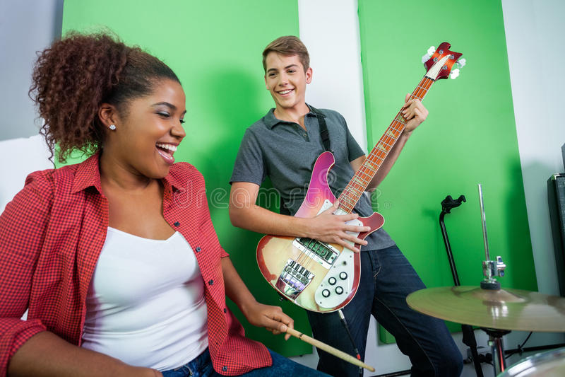 Гитарист выполняя пока смотрящ барабанщика стоковые изображения