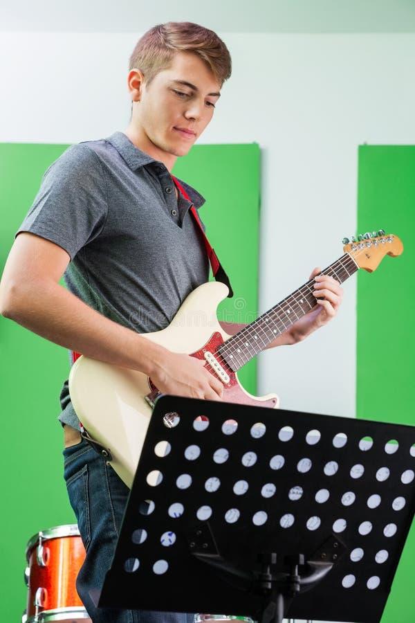 Гитарист выполняя пока смотрящ мюзикл стоковое фото