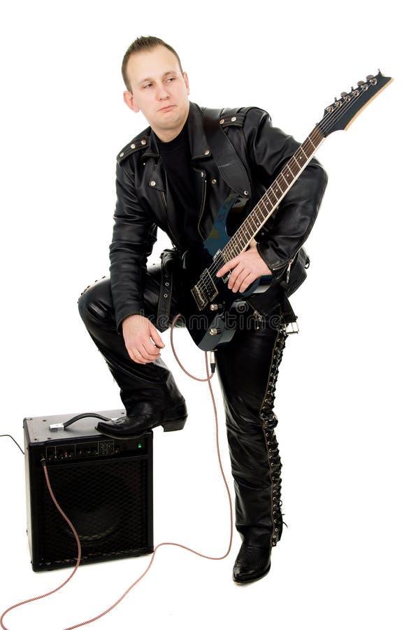 Гитарист в кожаных одеждах, гитара утеса Гая игр стоковое изображение rf