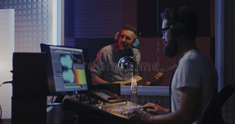 Гитарист и звукооператор работая в студии стоковые изображения rf