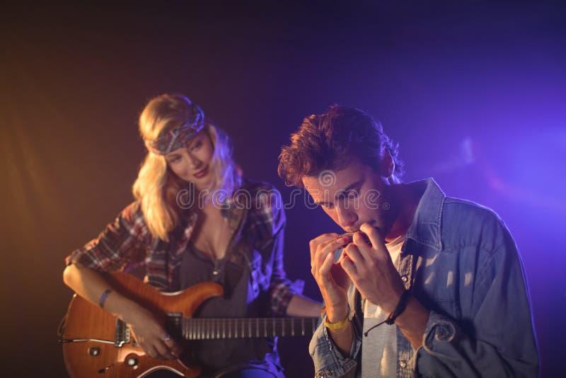 Гитарист смотря музыкант играя губную гармонику в концерте музыки стоковые изображения rf