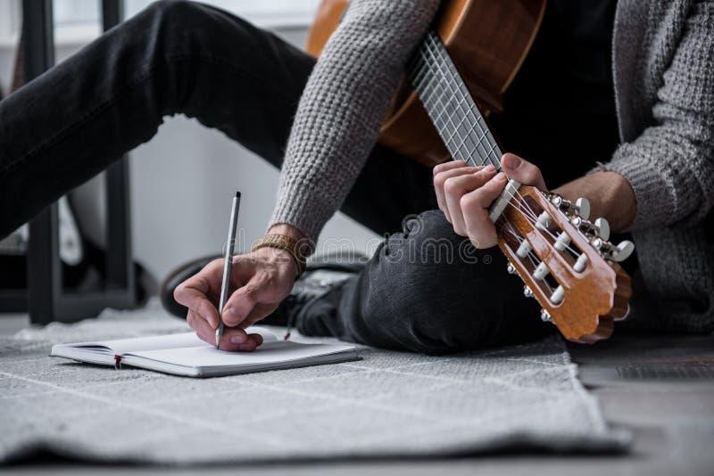 Гитарист составляя новую песню в квартире стоковая фотография rf