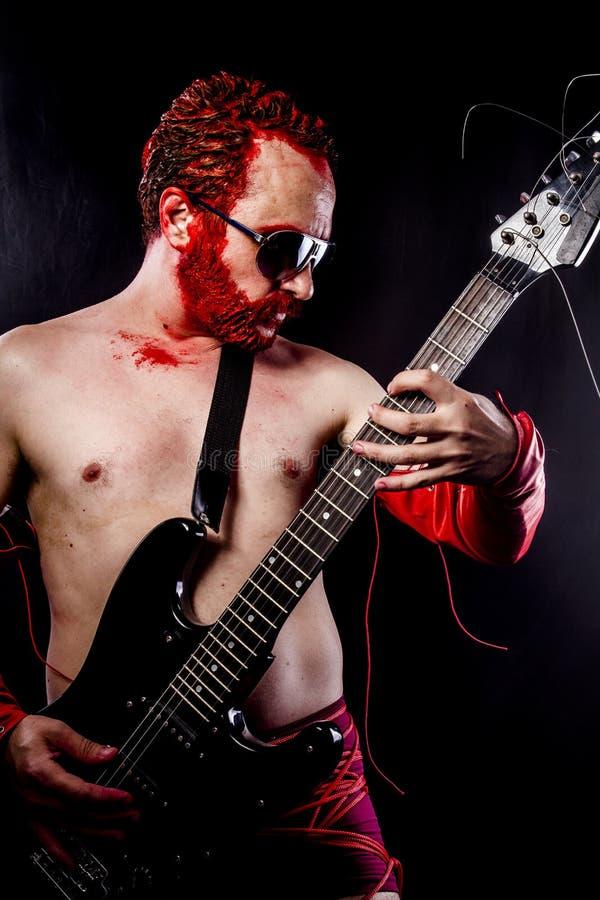 Гитарист с чернотой электрической гитары, нося краской стороны и красным цветом стоковое фото