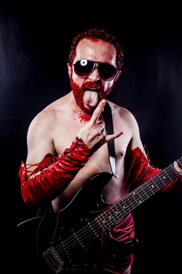Гитарист с чернотой электрической гитары, нося краской стороны и красным цветом стоковые фотографии rf