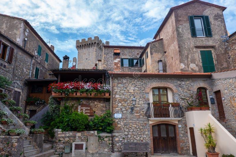 Главная площадь меньшего средневекового городка Capalbio, Тосканы, Италии, со зданиями и цветками стоковые фотографии rf