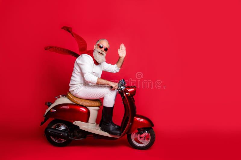 Гладкий санта с седыми волосами движущийся отряд из винтажного мопеда носит белый джемпер и брюки изолированный красный фон стоковая фотография