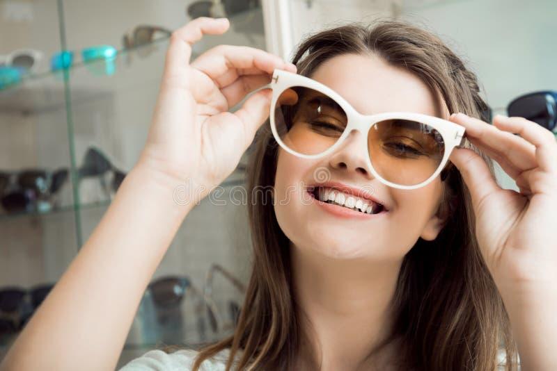 Глаза заслуживают самые лучшие объективы и стекла Портрет симпатичной женщины в магазине optician выбирая новые пары стильного стоковые изображения rf