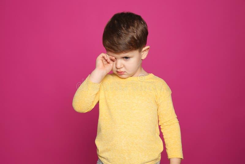 Глаз затирания мальчика на предпосылке цвета стоковое фото rf