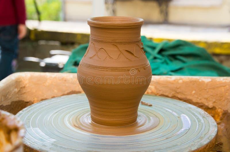 Глиняный горшок на колесе гончарни стоковые изображения