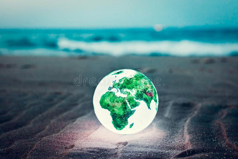 Глобус земли накаляя на пляже вечером стоковые фотографии rf