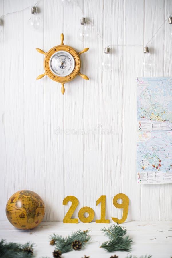 Глобус около 2019 на белой деревянной предпосылке стоковая фотография