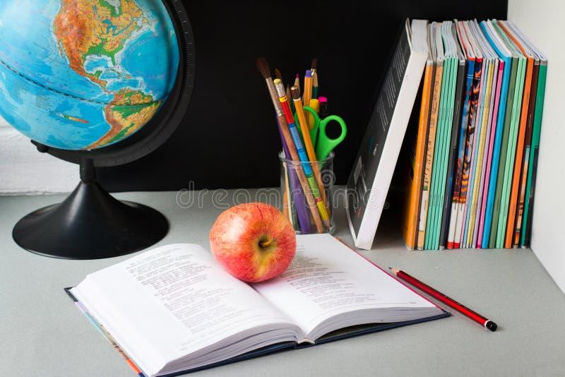 Глобус, стог тетради, карандаши и яблоко на таблице Аксессуары исследований школьника и студента r стоковые изображения