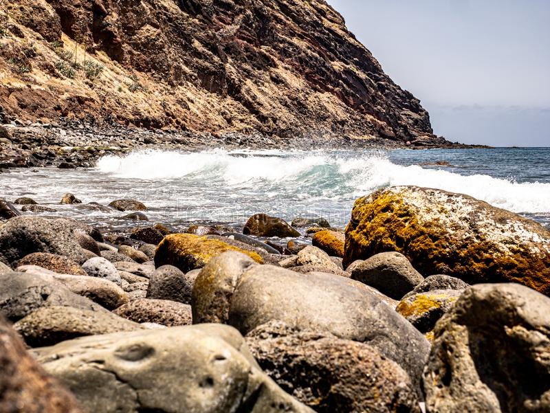 Глубокий взгляд над скалистым пляжем с входящей волной стоковое фото rf