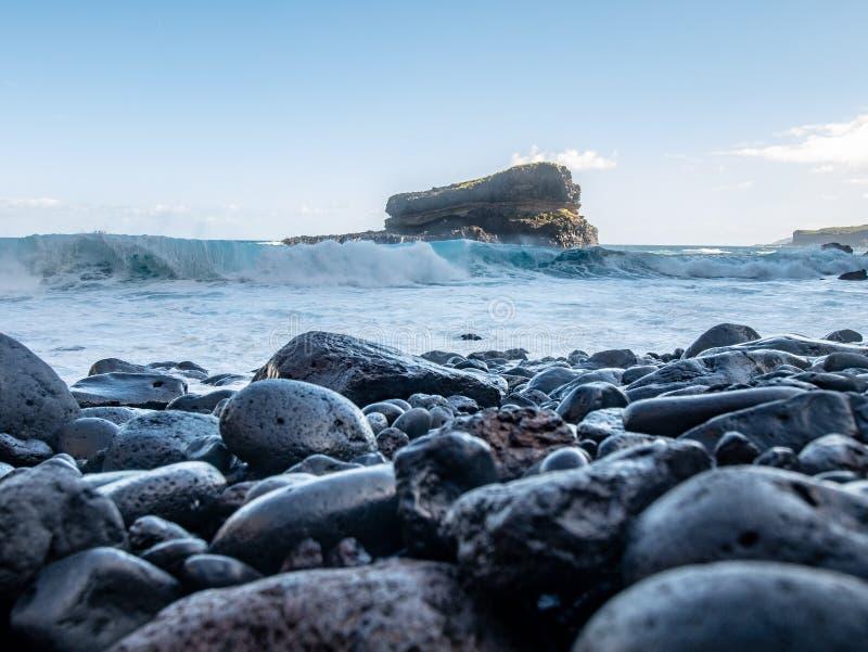 Глубокий взгляд от каменного пляжа к утесу в море стоковое изображение rf