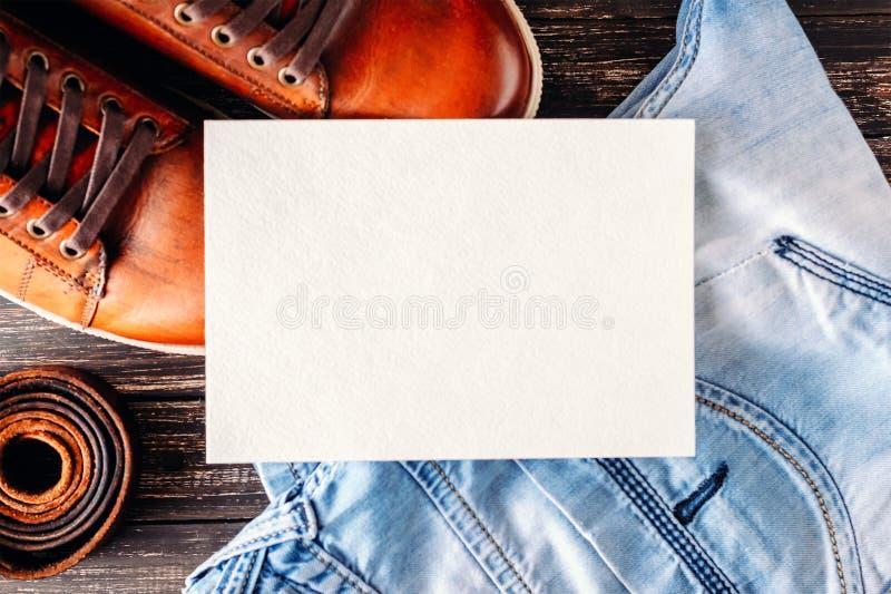 Глумитесь вверх мужских коричневых кожаных ботинок, голубых джинсов и пояса с белым чистым листом стоковое фото rf