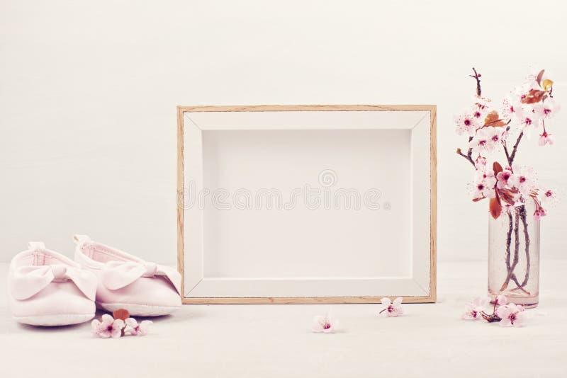 Глумитесь вверх с пустой картинной рамкой, розовыми нежными цветками весны и небольшими ботинками ребенка стоковое фото