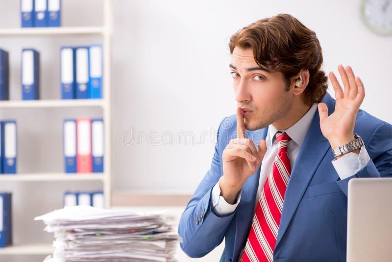 Глухой работник используя слуховой аппарат в офисе стоковое фото