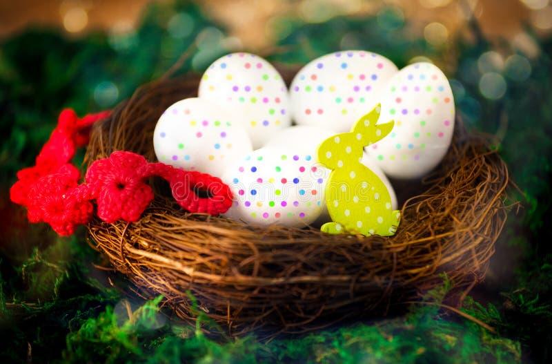 Гнездо с красочными яичками и желтым кроликом на зеленом мхе для пасхи стоковое изображение rf