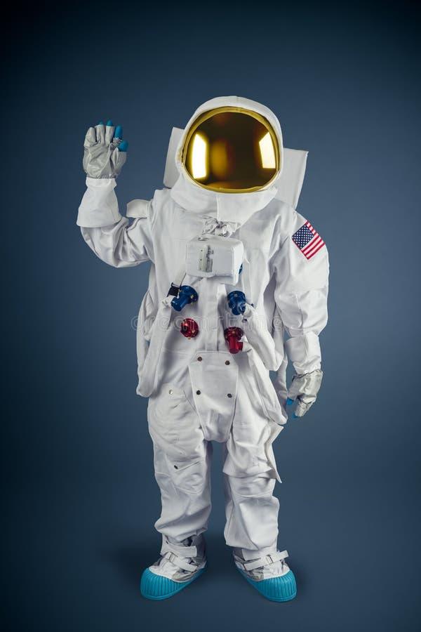Говорить астронавта высокий на серой предпосылке стоковое изображение rf
