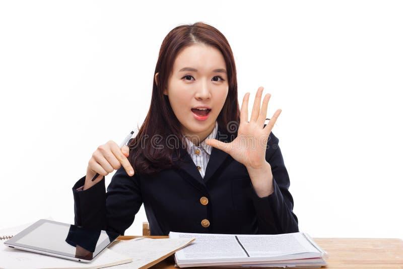 Говорить молодому азиатскому студенту на столе. стоковые фото