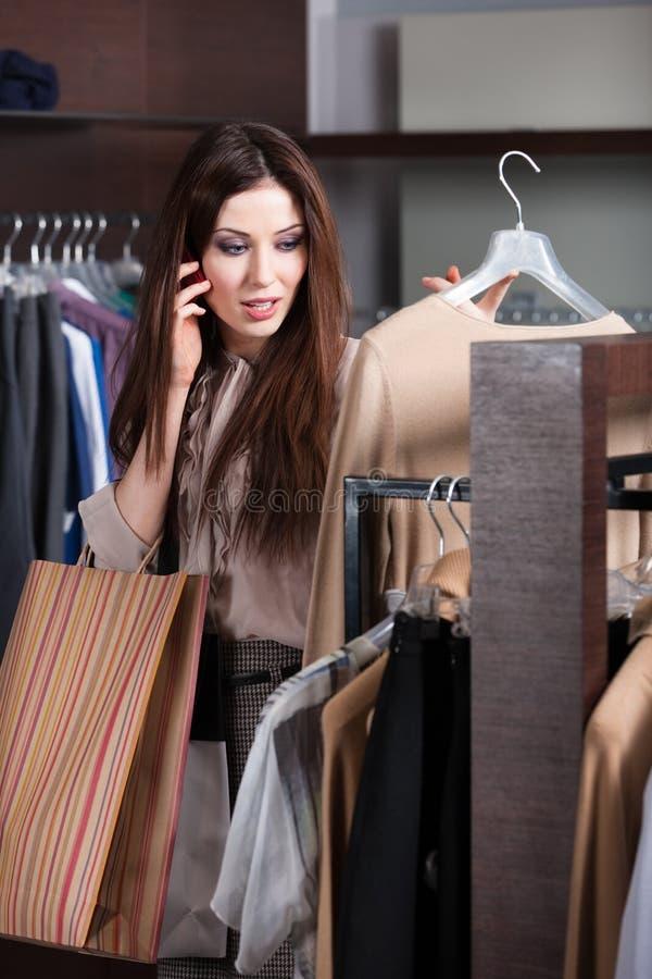 Говорить на мобильном телефоне и выбирать одежды стоковое изображение