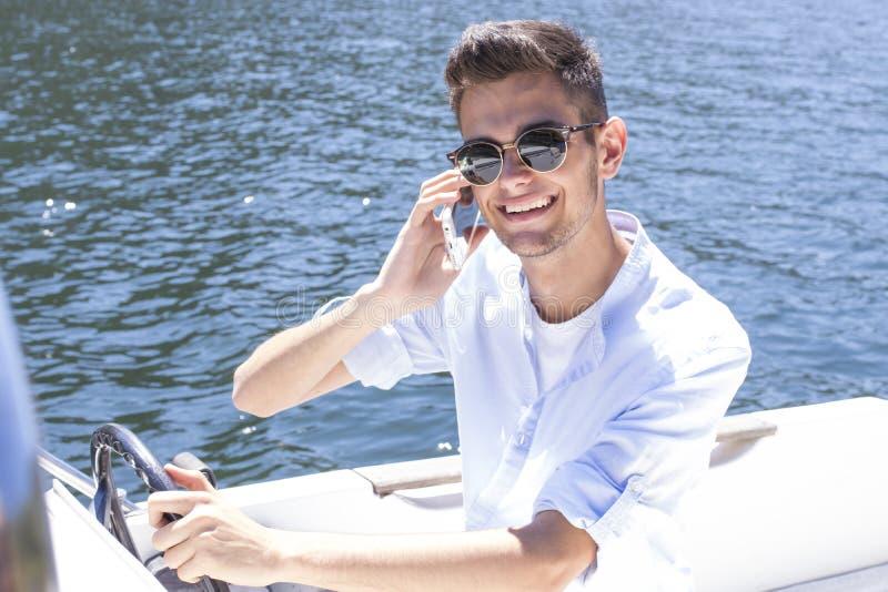 Говорить на телефоне на яхте стоковые фотографии rf
