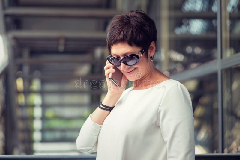 Говорить на усмехаться телефона стоковые фотографии rf
