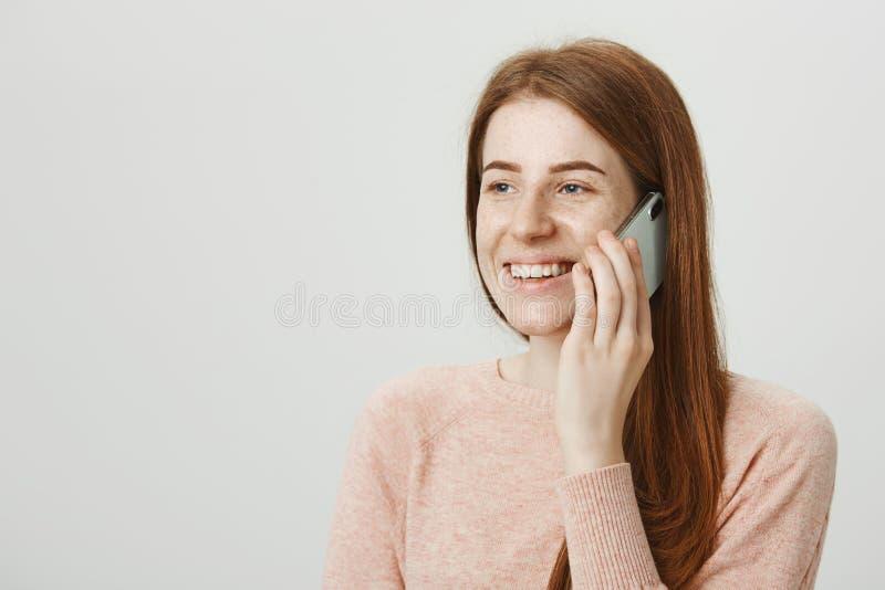 Говорить симпатичного redhead женский на smartphone пока смотрящ в сторону и усмехающся жизнерадостно, стоящ над серым цветом стоковая фотография