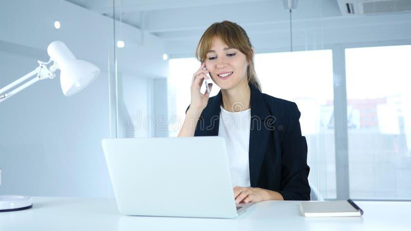 Говорящ на телефоне, молодой женский присутствуя на звонок на работе стоковые фотографии rf