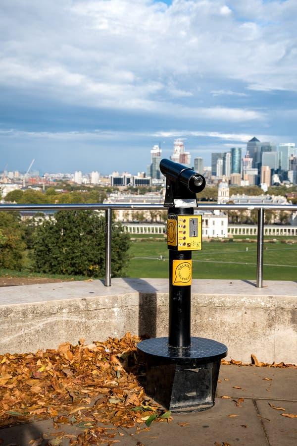 Говоря телескоп на смотровой площадке в парке Гринвич королевском с взглядом на доме ферзя и городе Лондона стоковые фото