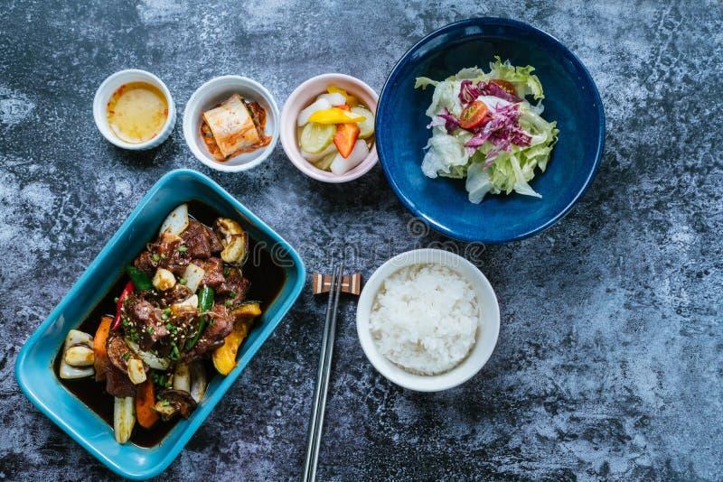 Говядина окунула в остром соусе с рисом и салатом в шаре стоковое фото rf
