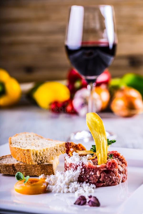 говядина сырцовая Вкусное tartare стейка Классическое tartare стейка на белой плите с хлебом яичка и вином чашки красным стоковая фотография rf
