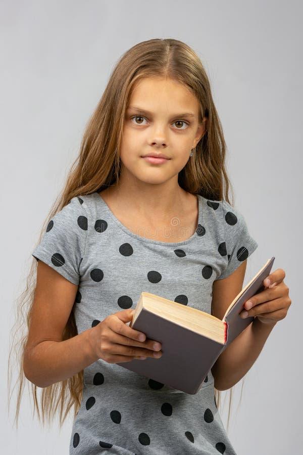 Годовалая девушка красивые 10 читает книгу и взгляды в рамку стоковые изображения